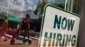 A ''Now Hiring'' sign is seen in the store front window in Miami, Fla.